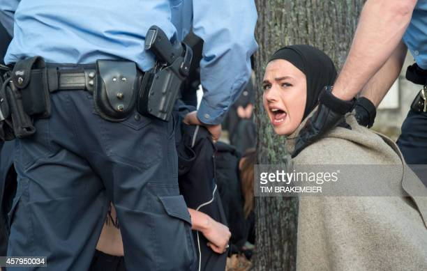Police officers evacuate an activist from the women rights organization FEMEN during a protest in front of the Iranian embassy in Berlin on October...
