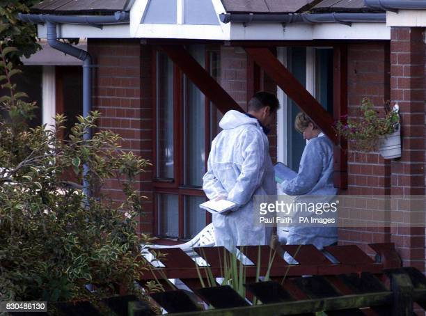 Police officers examine the scene of a shooting in North Belfast where a man was shot and killed in a new gun attack linked to the feud between rival...