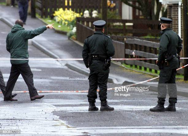 Police officers examine the scene where a Catholic taxi driver was shot dead in Donaghmore Co Tyrone Northern Ireland Police said they were still...