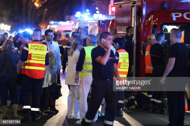 Police officers firefighters and rescue workers are seen at the site of an attack on the Promenade des Anglais on July 15 after a truck drove into a...