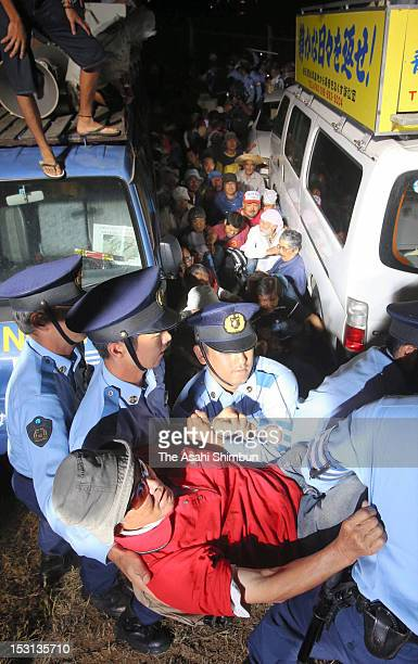 Police officers forcibly remove a protester at the gate of the US Marine Corps Futenma Air Station on September 30 2012 in Ginowan Okinawa Japan...