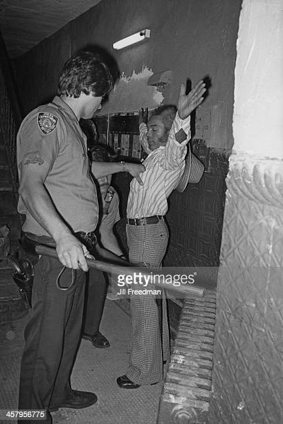 Police officers frisk a suspect in an apartment hallway in the Lower East Side New York City circa 1978