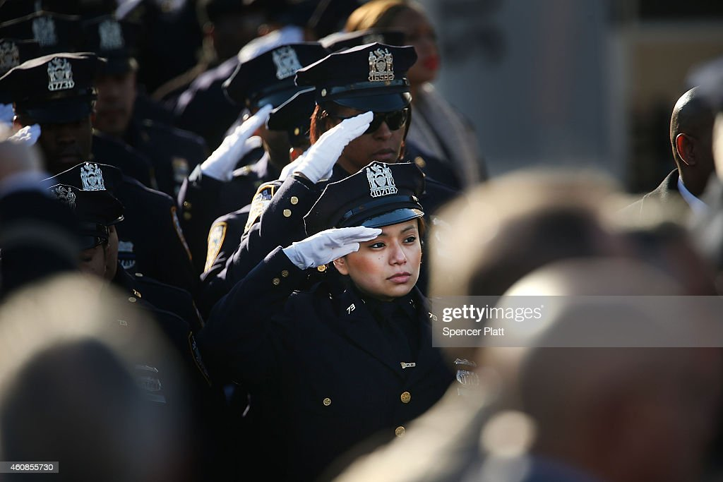 Police officers from around the country salute outside of Christ Tabernacle Church for the funeral of slain New York City Police Officer Rafael Ramos...