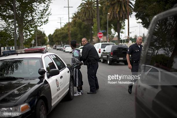 Police officers from the Los Angeles Police Department Counter Surveillance Team and gang units take into custody two Bloods street gang members for...