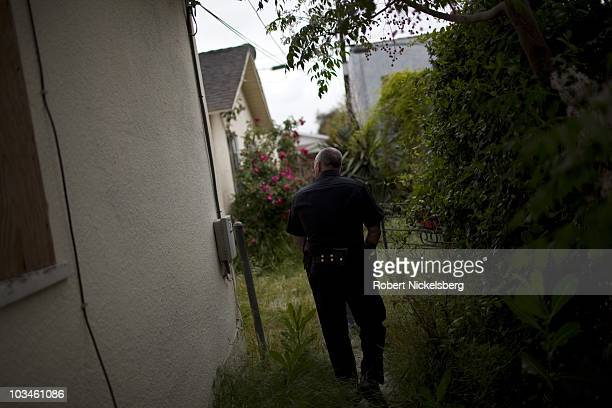Police officers from the Los Angeles Police Department Counter Surveillance Team and gang units search a vacant home after taking into custody two...