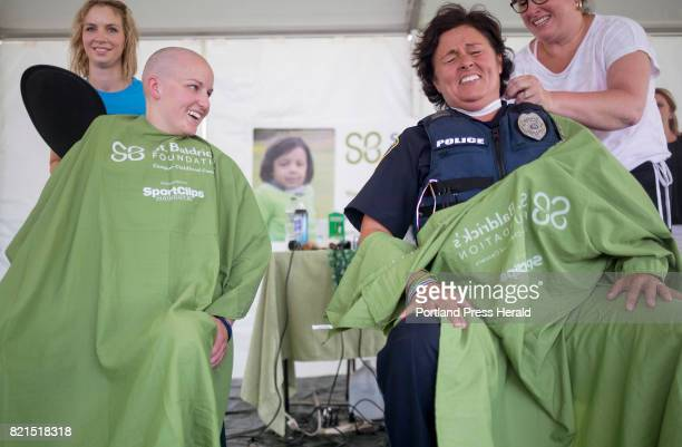 Police officers from Westbrook from left Jaci Lorenzen and Sally Mailman laugh as they both have their heads shaved to raise money for St Baldrick's...
