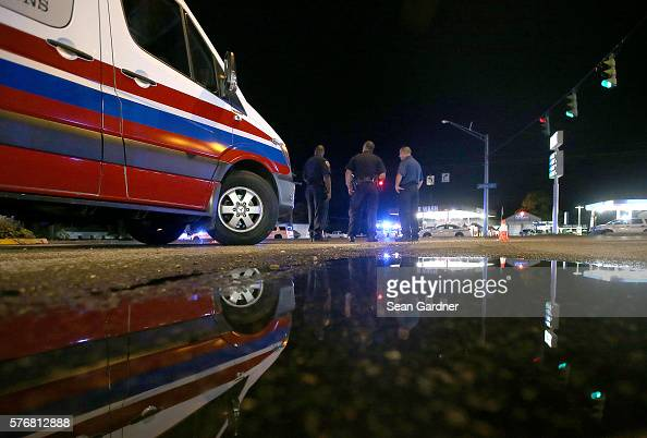 Police officers gather near the scene of the crime where three police officers were killed this morning on July 17 2016 in Baton Rouge Louisiana The...