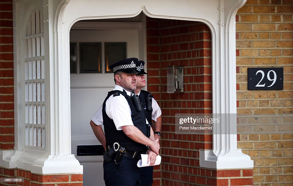 Police officers guard a house in New Malden on April 23, 2014 in south London, England. Police say that a 43 year old woman has been arrested after the bodies of three children were found at a property last night.