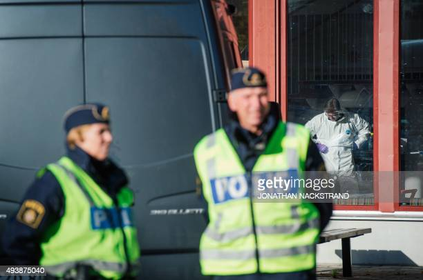 Police officers guard as a forensic staff investigates inside the primary and middle school Kronan in Trollhattan southwestern Sweden on October 23...