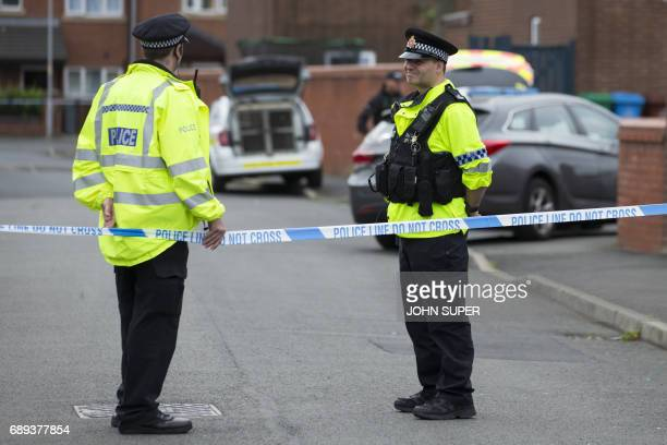 Police officers guard the entrance to a street in the Moss Side area of Manchester on May 28 2017 during an operation A British minister said Sunday...