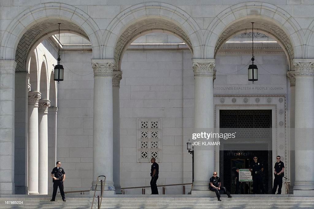 Police officers guard the entrance to City Hall as demonstrators seeking change in immigration policy march on May Day in Los Angeles, California, May 01, 2013. Some 2,000 demonstrators marched in May Day rallies calling for immigration reform, a key issue just north of the US-Mexican border.