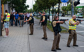 Police officers guard with guns as other officers escort people from inside the shopping center as they respond to a shooting at the Olympia...