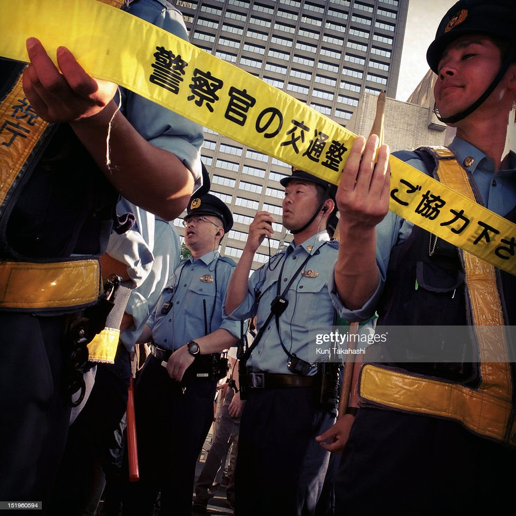 Police officers hold a tape to control anti-nuclear protesters during a mass demonstration on July 29, 2012 in Tokyo, Japan. Police have imposed tight controls on the weekly protest against restarting nuclear power plants. All 54 of Japan's nuclear plants had been offline for months, in the wake of the disaster at the Fukushima Daiichi nuclear plant. Protesters wanted the government to reconsider its energy policy but the government decided to restart the Ohi nuclear plant anyway.
