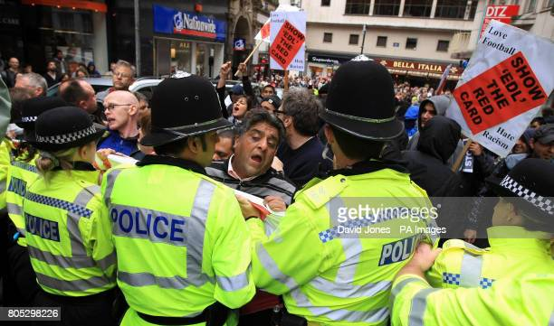 Police officers hold back members of the public who are holding their own protest during the English Defence League demonstration in Birmingham
