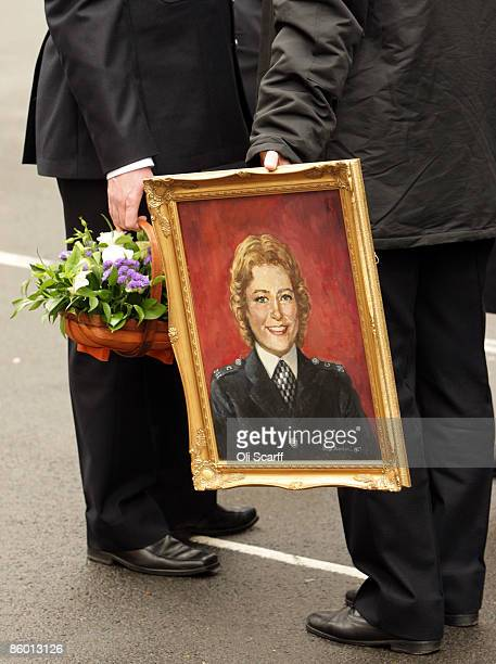 Police officers hold flowers and a portrait of Yvonne Fletcher prior to a ceremony to mark the 25th anniversary of the killing of WPC Yvonne Fletcher...