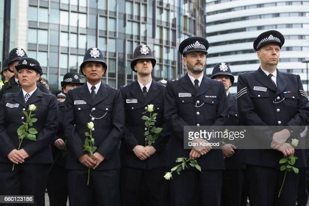 Police officers hold flowers on Westminster Bridge during a vigil to remember the victims of last week's Westminster terrorist attack on March 29...