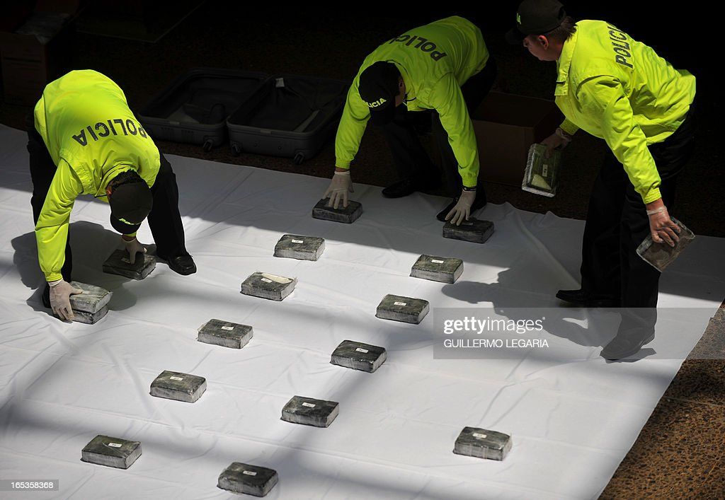 Police officers hold packages containing part of a seizure of 102 Kgs of cocaine, while being presented to the press in the Police heaquarters in Bogota, on April 3, 2013. The drug was seized in a house in the Bogota's neighborhood of Kennedy, and was ready to be marketed in Bogota and also be sent to Eldorado International Airport of Colombian capital, authorities said. AFP PHOTO/Guillermo Legaria