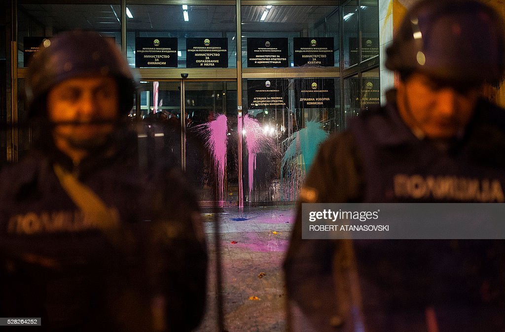 Police officers hold their shields while protesters pelt the facade of the building where the State Electoral Commission is placed, with colored paint in Skopje on May 4, 2016, during the series of protests dubbed Colorful Revolution. The country has been politically gridlocked for two years but the crisis rose a notch on April 12 when President Gjorge Ivanov halted a probe into more than 50 public figures suspected of involvement in corruption and a wire-tapping scandal. The move triggered street protests against Ivanov and the ruling party's leader, Nikola Gruevski. / AFP / Robert ATANASOVSKI