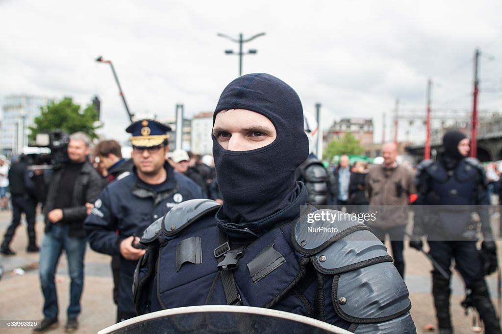 Police officers in anti riot gear have taken off their helmets, at the end of an anti government protest that turned into a riot in Brussels on May 24, 2016.