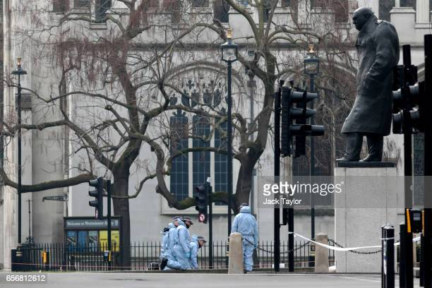 Police officers in forensics suits work at the scene following yesterday's attack in which one police officer was killed on March 23 2017 in London...
