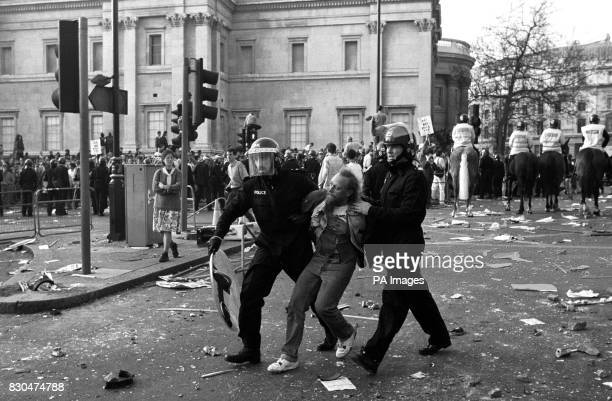 Police officers in riot gear arrest a protester near the National Gallery Trafalgar Square London after a demonstration against the Poll Tax...