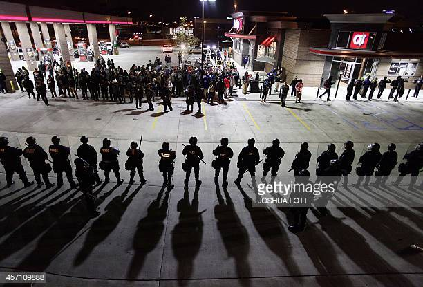 Police officers in riot gear hold a line as they watch demonstrators protest the shooting death of Michael Brown and 18yearold Vonderrit Myers Jr at...