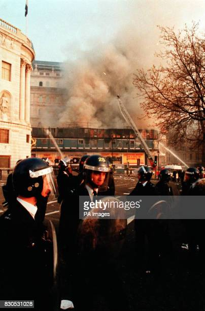 Police officers in riot gear stand in Trafalgar Square London after a protest against the socalled Poll Tax developed into a riot A building on the...