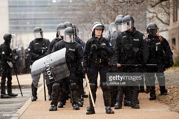 Police officers in riot gear stand outside city hall as demonstrators protest the shooting death of Michael Brown November 26 2014 in St Louis...