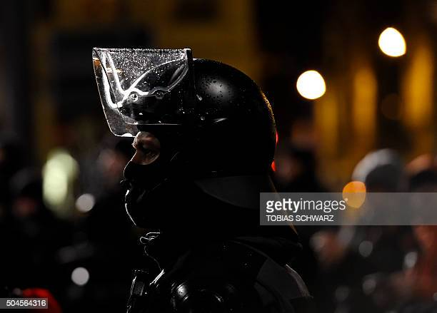 Police officers in riot gear watch protestors from the PEGIDA movement during a rally in Leipzig on January 11 2016 Supporters of the xenophobic...