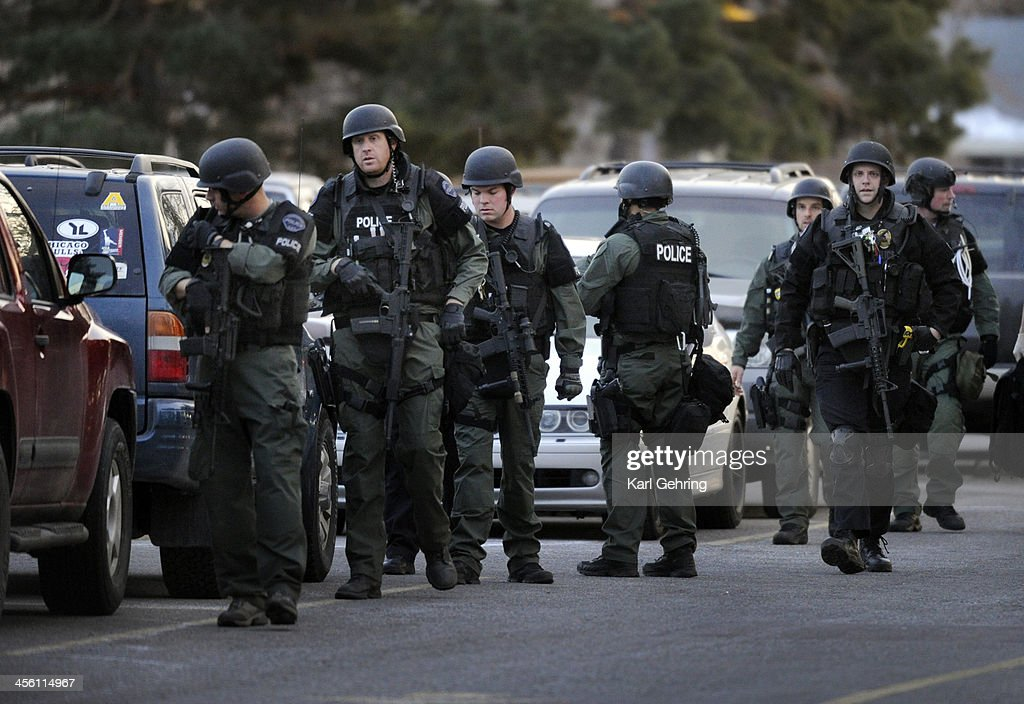 Police officers in tactical gear searched the student parking lot of Arapahoe High School Friday afternoon, December 13, 2013. A shooting inside the school sent hundreds of students rushing for safety. Photo By Karl Gehring/The Denver Post via Getty Images