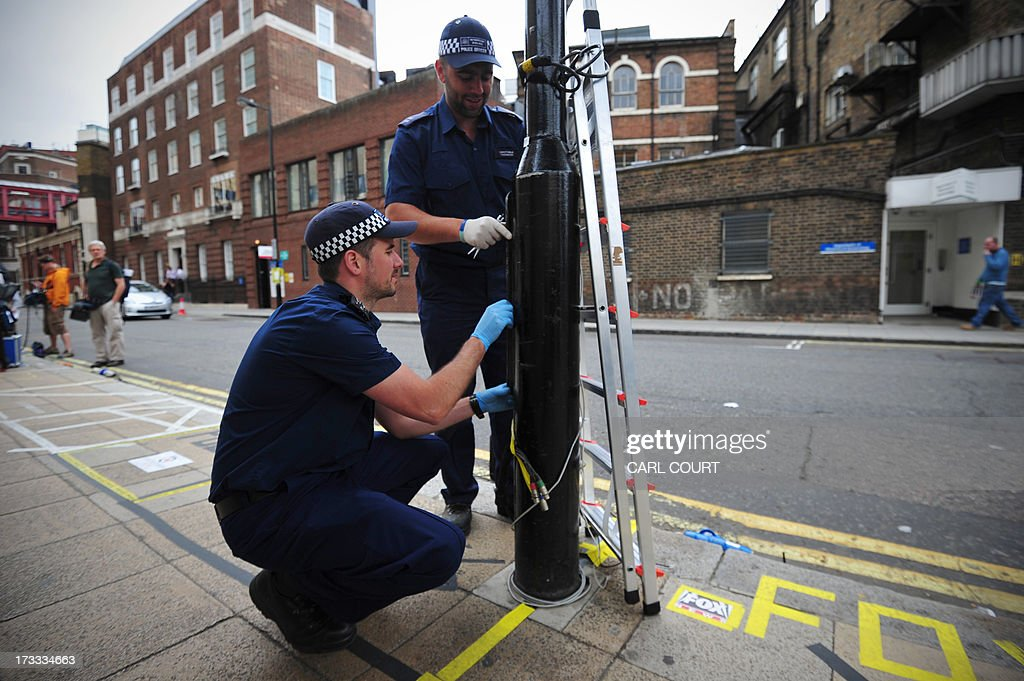 Police officers inspect a lamppost outside the Lindo Wing of Saint Mary's Hospital in London, on July 12, 2013, where Prince William and his wife Catherine's baby will be born. Britain's royal family and the world's media are on tenterhooks awaiting the birth of Prince William and wife Catherine's first child, a baby who will one day be king or queen of Britain and a diverse group of commonwealth countries.