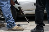 Police officers inspect an AK47 assault rifle found in a taxi with a dead woman inside after a shooting involving police in Acapulco Guerrero State...