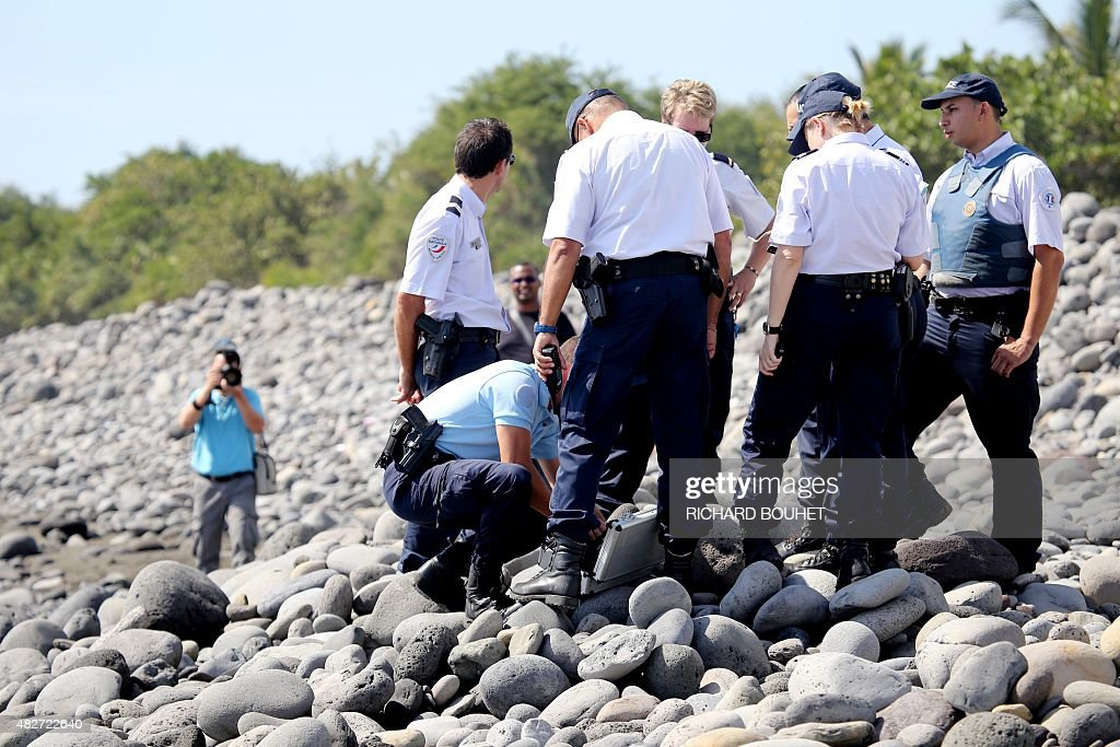 Police officers inspect metallic debris found on a beach in SaintDenis on the French Reunion Island in the Indian Ocean on August 2 close to where a...