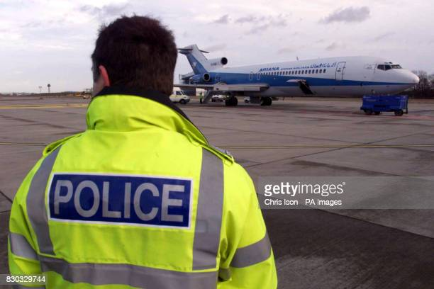 Police officers inspect the hijacked Afghan Ariana 727 plane as it sits on the tarmac at Stansted Airport in Essex after the hijackers gave...