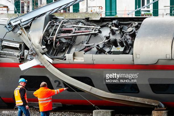 Police officers inspect the site of a train crash at the train station of Lucerne where a Eurocity train of Trenitalia derailed on March 22 2017 in...