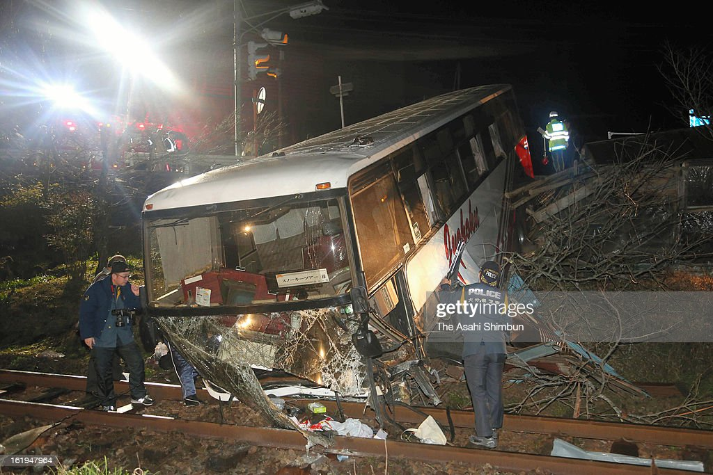 Police officers investigate a tourist bus crashed through guardrail and fell on to the tracks of Japan Railway Kyudai Honsen line, on February 17, 2013 in Kokonoe, Oita, Japan. 42 passengers and driver were injured.