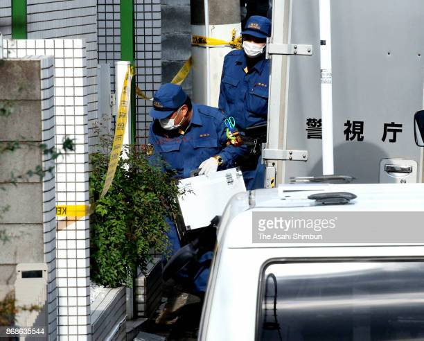 Police officers investigate an apartment building where the severed body parts of nine people were found on October 31 2017 in Zama Kanagawa Japan A...