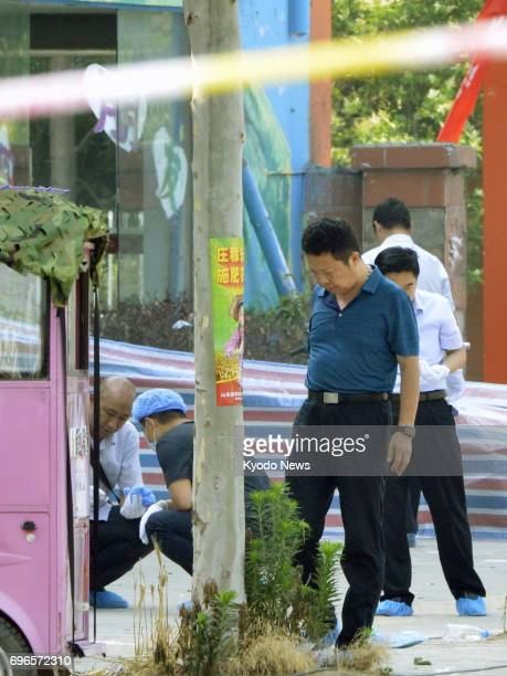 Police officers investigate at the entrance of a kindergarten in Xuzhou China on June 16 where an explosive device went off and killed at least eight...