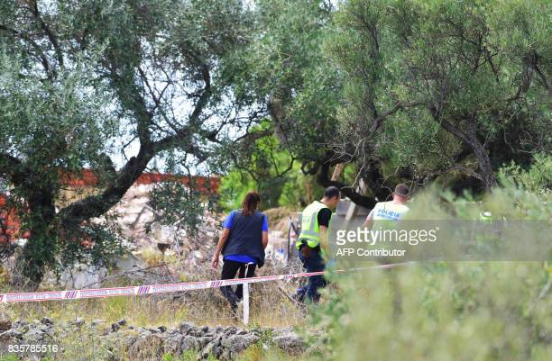 Police officers investigate the rubble of a house where suspects of this week's twin assaults in Spain were believed to be building bombs in Alcanar...
