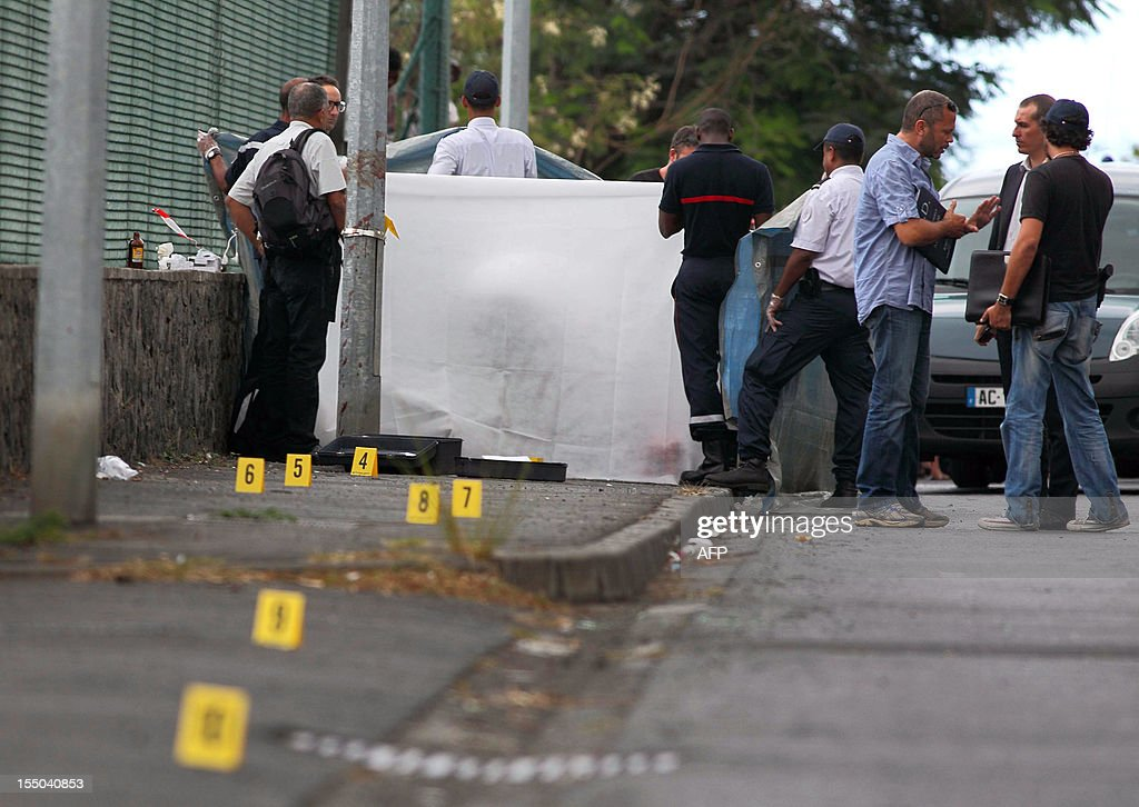 Police officers investigate the scene where a 16-year-old boy was stabbed to death after school , on October 30, 2012 , in Le Port, on the French island of La Reunion in the Indian Ocean. According to witnesses, the high school student was stabbed 10 times, on his way home, by a fellow student with whom he had a disagreement.