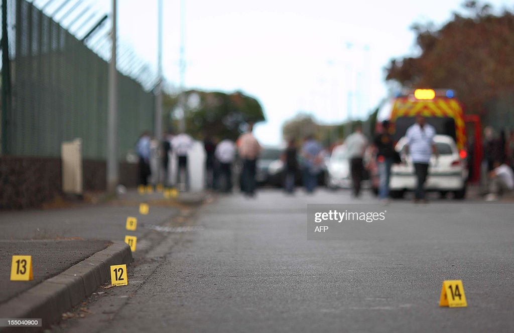 Police officers investigate the scene where a 16-year-old boy was stabbed to death after school , on October 30, 2012 , in Le Port, on the French island of La Reunion in the Indian Ocean. According to witnesses, the high school student was stabbed 10 times, on his way home, by a fellow student with whom he had a disagreement. AFP PHOTO