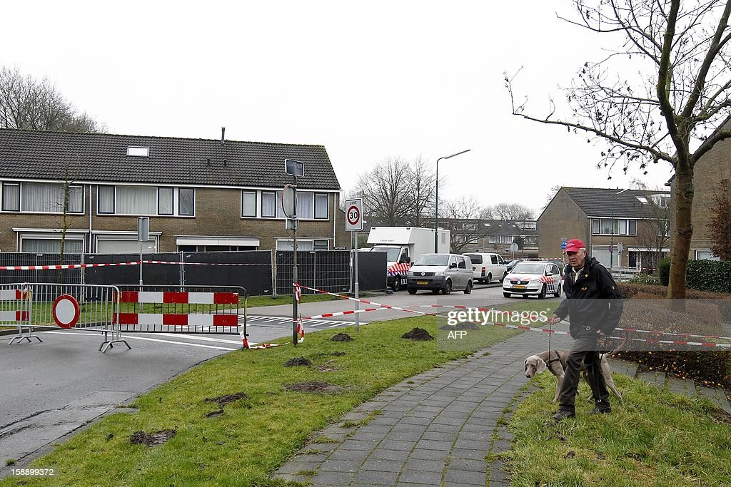 Police officers investigate the surrounding of the house where a 16-year-old girl was stabbed to death in IJsselstein on January 3, 2013. A 42-year-old woman has been arrested. AFP PHOTO / ANP - BAS CZERWINSKI = netherlands out -
