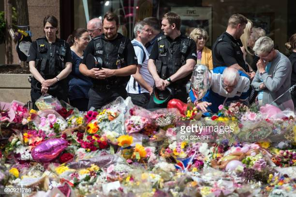 Police officers join members of the public to view the flowers and messages of support in St Ann's Square in Manchester northwest England on May 31...