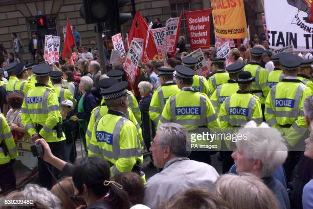 Police officers keep a close watch on a demonstration against tuition fees at the Mound in Edinburgh as the Queen's procession approaches up the...