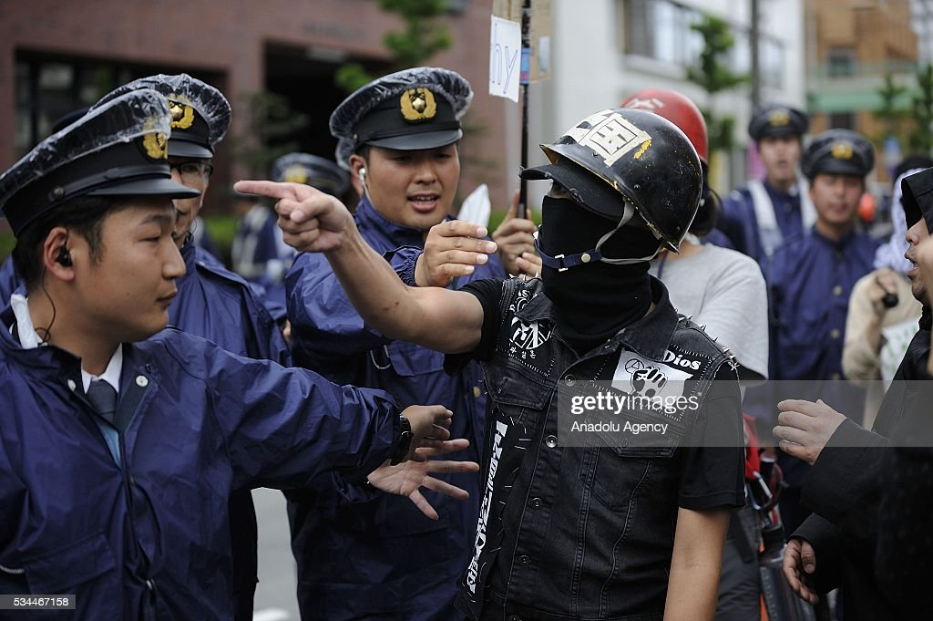 Police officers keep guard as the protesters take part in a demonstration against the G7 Summit on May 26, 2016 in Tsu City, Mie Prefecture, Japan, while G7 Summit 2016 is held in Ise-Shima in Mie Prefecture in Japan during two days from May 26 to 27.