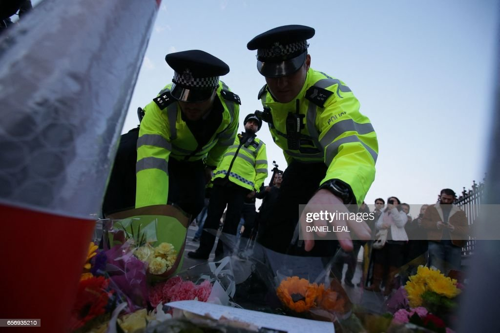 TOPSHOT - Police officers lay flowers in honour of the victims of the March 22 terror attack at the end of Westminster Bridge by the Houses of Parliament in central London on March 23, 2017 after the bridge reopened. Britain's parliament reopened on Thursday with a minute's silence in a gesture of defiance a day after an attacker sowed terror in the heart of Westminster, killing three people before being shot dead. Sombre-looking lawmakers in a packed House of Commons chamber bowed their heads and police officers also marked the silence standing outside the headquarters of London's Metropolitan Police nearby. PHOTO / Daniel LEAL