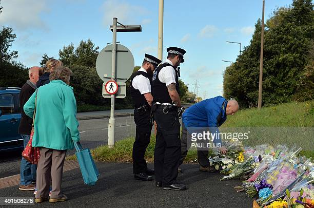 Police officers lay flowers near to the scene in Wallasey northwest England on October 6 2015 where Merseyside Police officer David Phillips was...