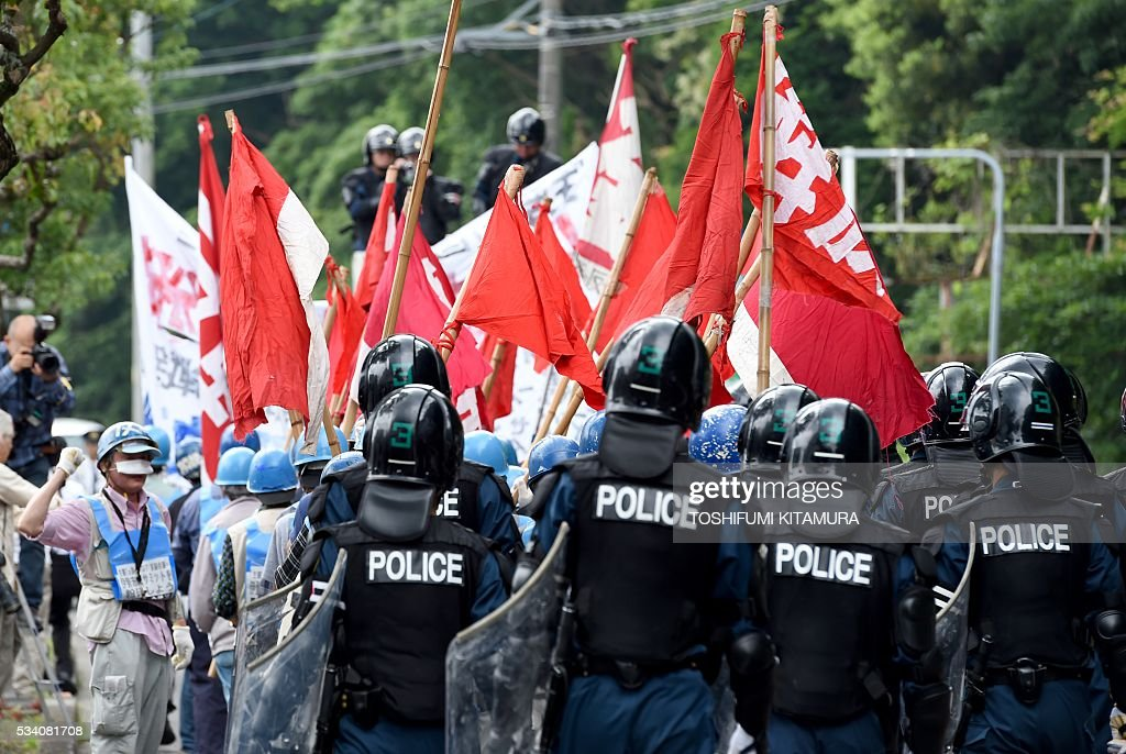 Police officers lead some 28 anti-G7 summit protesters in Shima city, Mie prefecture on May 25, 2016. Japan is on high-alert ahead of a Group of Seven summit with thousands of police on the streets of Tokyo and fanning out across the country as authorities boost security to unprecedented levels. / AFP / TOSHIFUMI