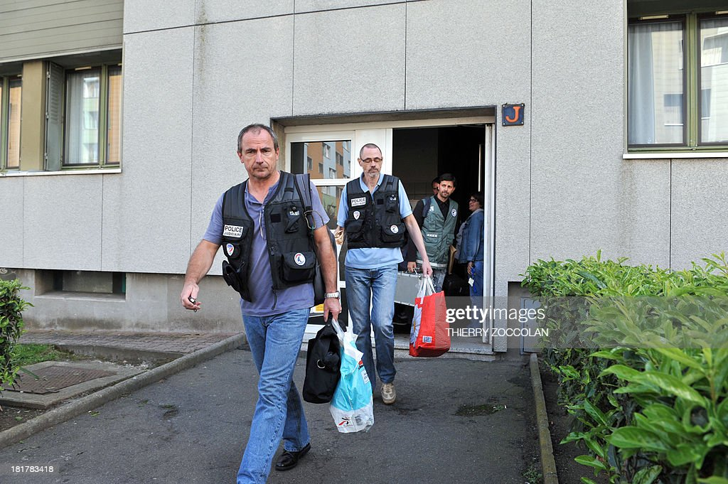 Police officers leave the appartment where lives the mother of Fiona, a five-year old girl who disappeared last May 12, after an investigation, on September 25, 2013 in Clermont-Ferrand.