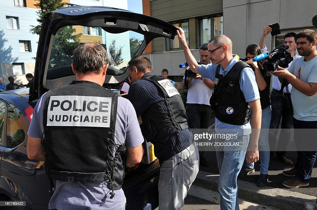 Police officers leave the appartment where lives the mother of Fiona, a five-year old girl who disappeared last May 12, after an investigation, on September 25, 2013 in Clermont-Ferrand. AFP PHOTO THIERRY ZOCOLAN